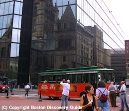 Photo of Boston Trolley Tour in Copley Square with Trinity Church reflected in glass sides of John Hancock Tower