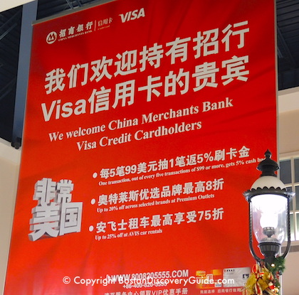 Sign stating that Wrentham Village stores accept certain Chinese credit cards
