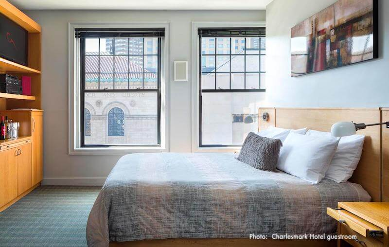 Guestroom in Charlesmark Hotel, with window views of the Boston Public Library