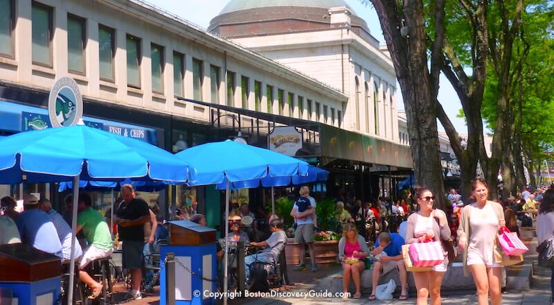 Shoppers and diners enjoying Faneuil Markeplace on a sunny afternoon