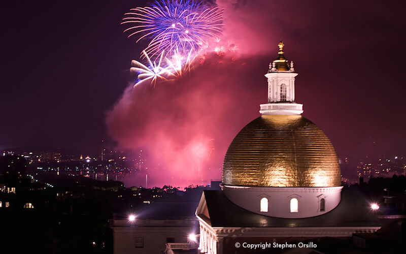 Boston fireworks, seen with the golden dome of the Massachusetts Statehouse in the foreground