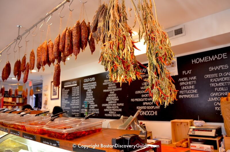 Sausages and chilis hanging over the meat counter n Bricco Salumeria in Boston's North End