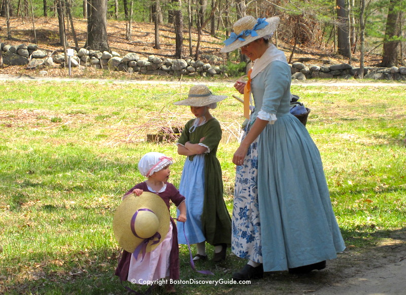 Reenactor portraying a Colonial woman with two young daughters during Patriots Day celebration