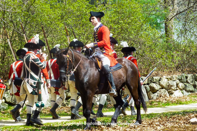 Reenactors portraying British troops march toward a 1775 battlesite at Minute Man National Historic Park