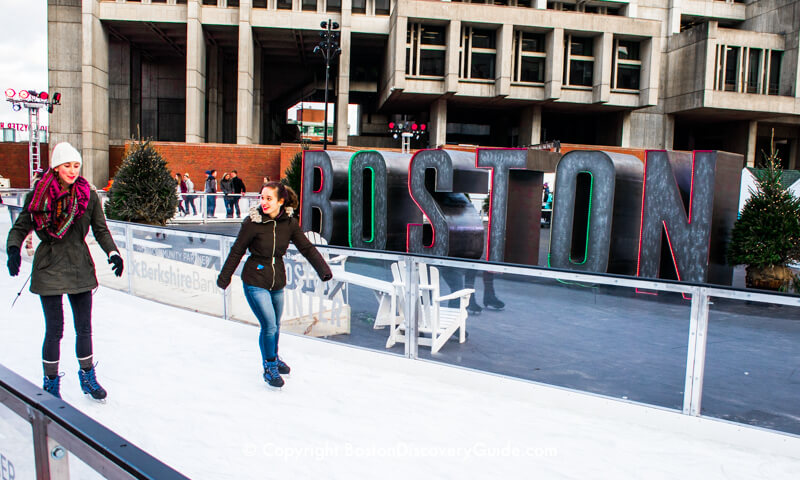 Winter Market ice skaters in front of the neon Boston sign