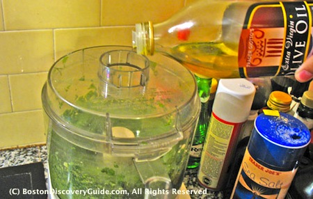 Add olive oil to basil pesto in a slow stream while food processor is running