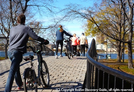 Bike riders crossing a small bridge over the Boston Esplanade's lagoon
