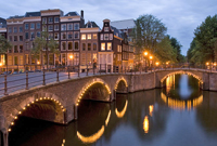 Canal and bridge in Amsterdam at dusk / Cruises from Boston to Europe - www.boston-discovery-guide.com