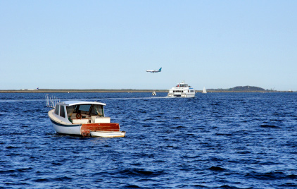 Photo of water taxi (in back) heading across Boston Harbor toward Boston Logan Airport