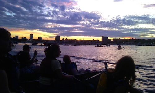 Photo of people waiting by the Charles River for Boston fireworks to begin