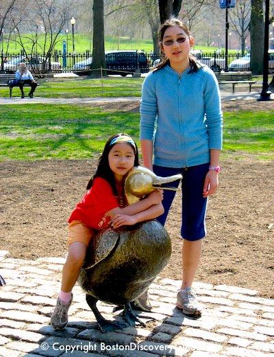 Children posing by Make Way for Ducklings statues in Boston's Public Garden