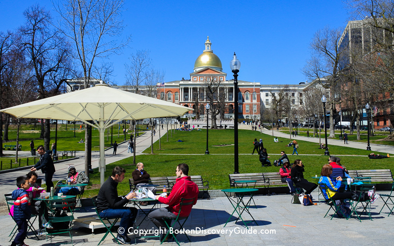 Tables and park benches on Boston Common in front of the Massachusetts State House