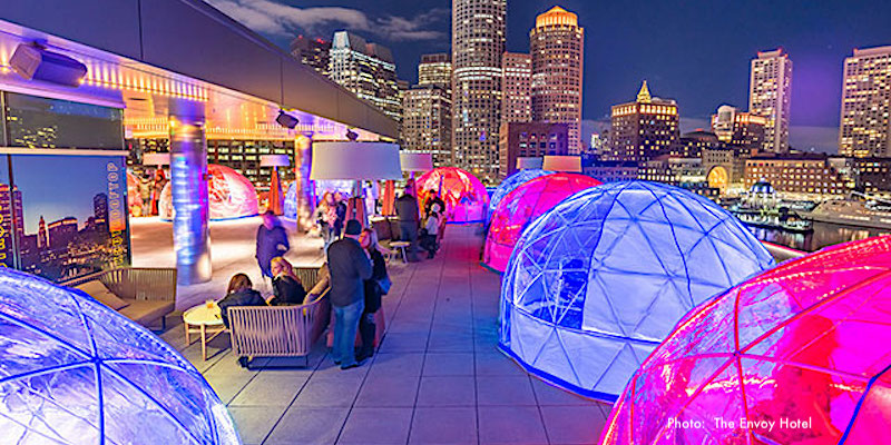 Igloos enclosing tables and chairs on The Envoy's rooftop bar