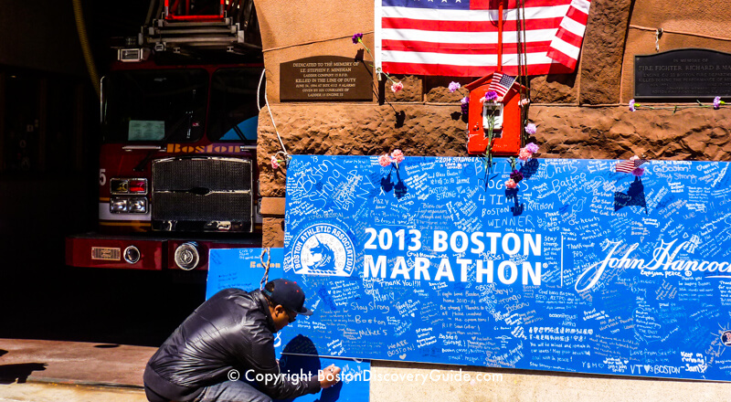 Messages transform a Boston Marathon sign into a memorial at the Engine 33/Ladder 15 firehouse
