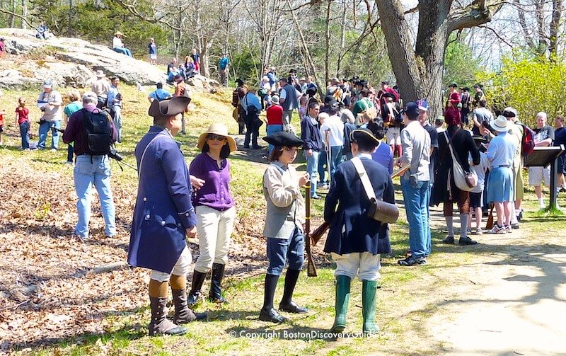 Colonial Reenactors mingle with spectators during a reenactment of a battle with the British as they fled back to Boston