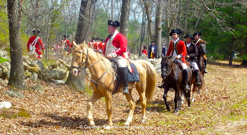 Reenactors portraying British Redcoats as they began their retreat back to Boston from Concord