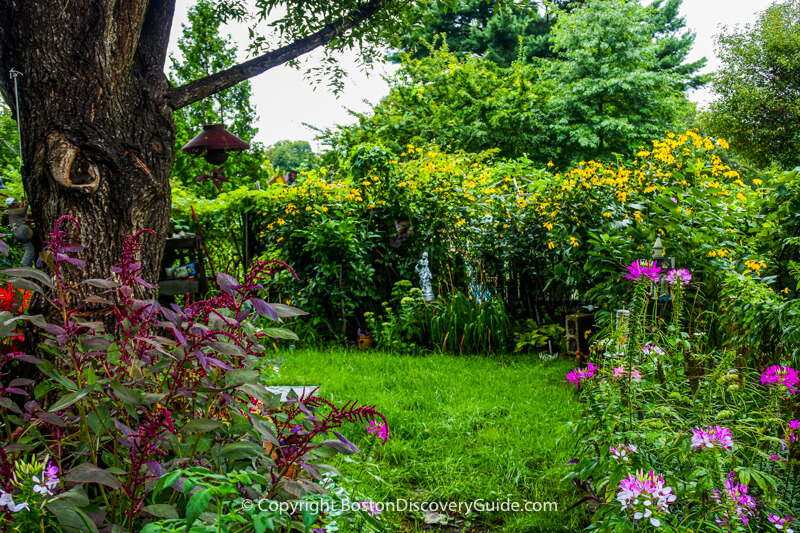 This pastoral garden focuses on a grassy lawn, beautiful flowers, bird feeders, and the small statue in the back