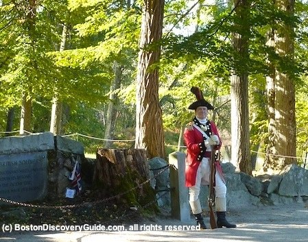 Redcoat reenactor standing next to British casualty memorial at Old North Bridge in Concord, MA