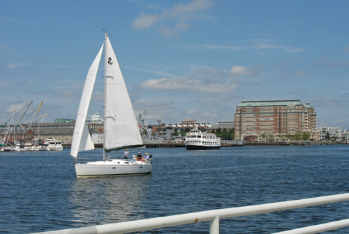 Sailboat and cruise boat seen from Boston's Harborwalk near Battery Wharf Hotel in the North End