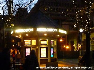 Bostix ticket booth in Faneuil Hall Marketplace, photographed on a December night with Christmas lights in the trees